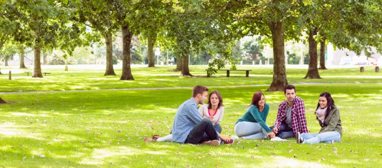 college students sitting on grass on campus